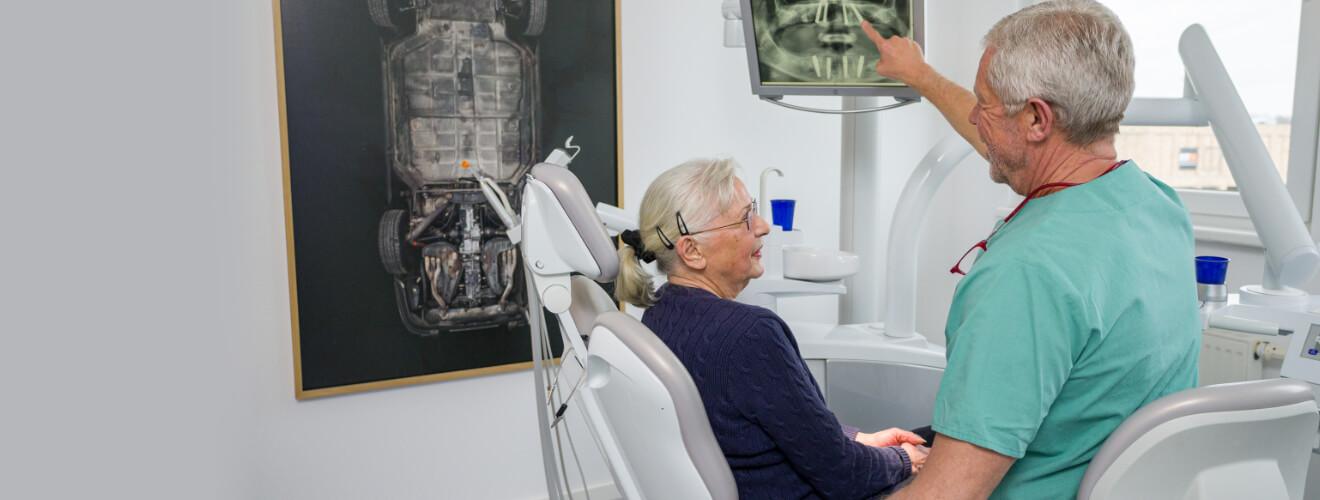 Zahnarzt zeigt Patientin All on 4 Lösung der Implantologie