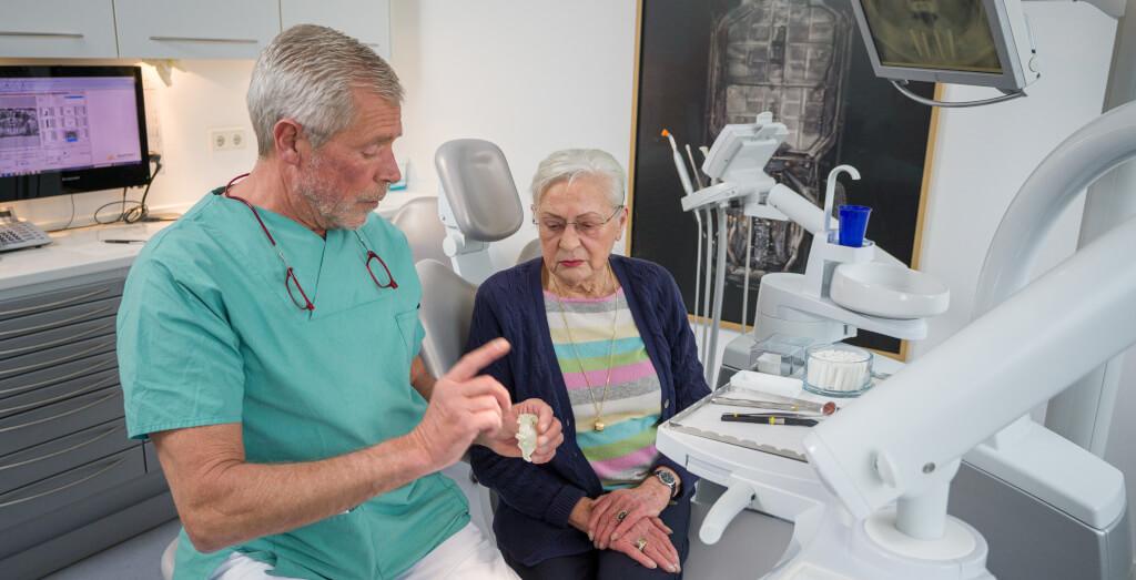 Zahnarzt berät Patientin zu Implantaten in Berlin