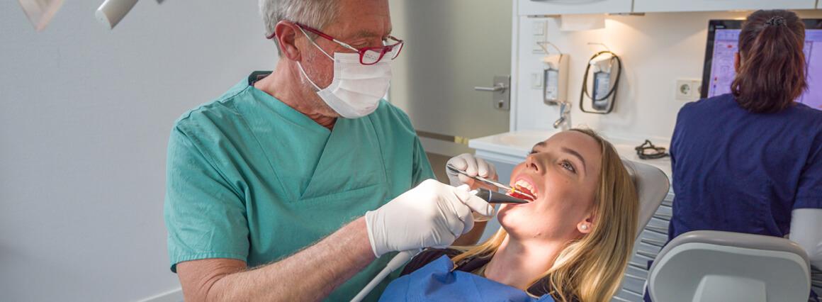 Zahnarzt bei der Weisheitszahnentfernung einer Patientin