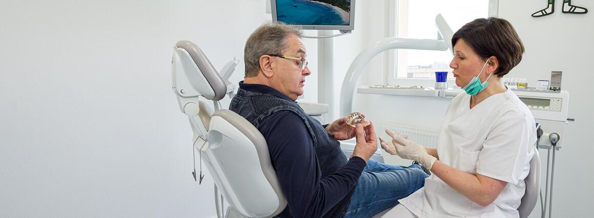 Zahnarzt erklärt Schritte der Zahnsanierungen